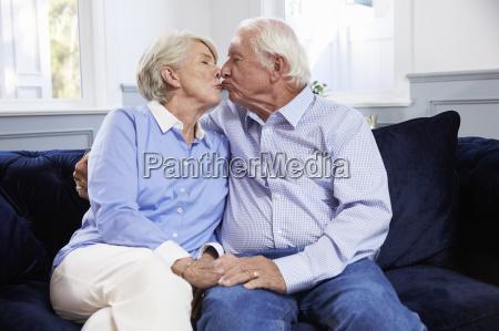 affettuosa coppia anziana seduta sul divano