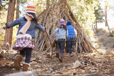 tre bambini giocano rifugio esterno fatto