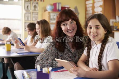 teacher and schoolgirl using tablet computer