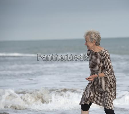 senior woman running from ocean wave