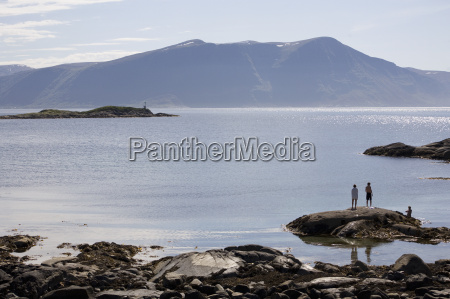 three people standing on fjord rocks