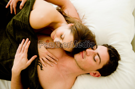 young couple hugging in bed