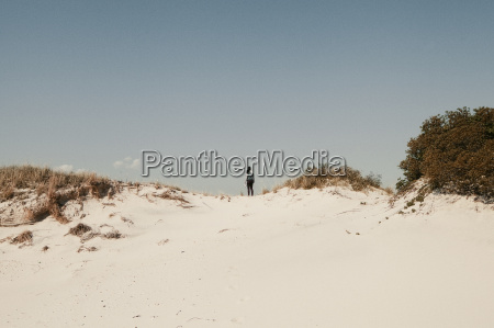 mid adult woman standing on sand