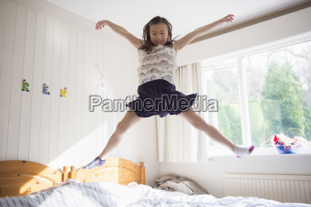 young girl jumping mid air on