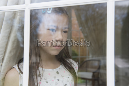 unhappy young girl looking out from