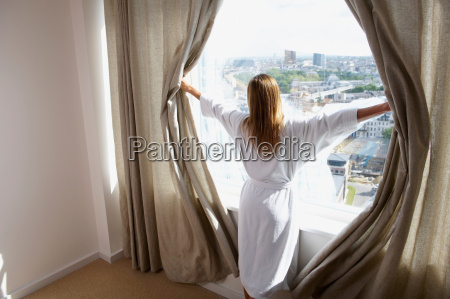 woman in her bathrobe opening curtains