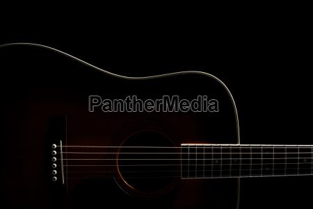 acoustic guitar against black background