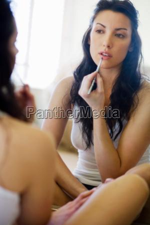 woman sitting by mirror applying make