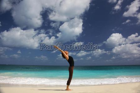 mature woman doing yoga on beach