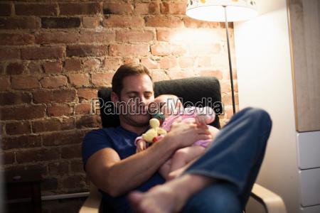 vater haelt baby tochter im sessel