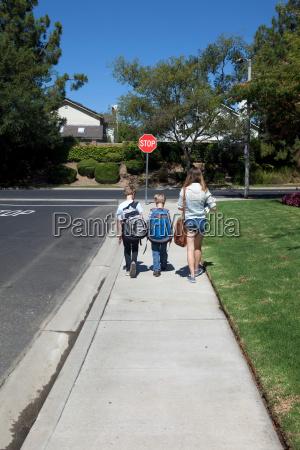 teenage girl walking brothers to school