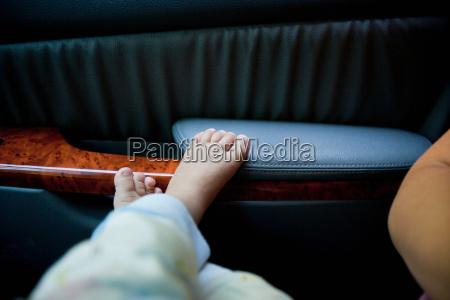 toddler boys feet on car door