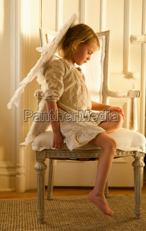 little girl on chair dressed as