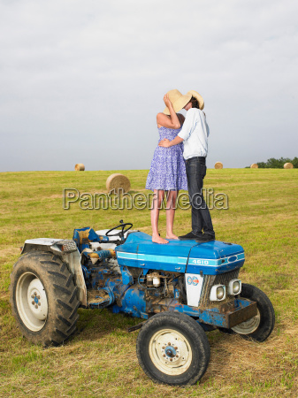 couple kissing on top of tractor