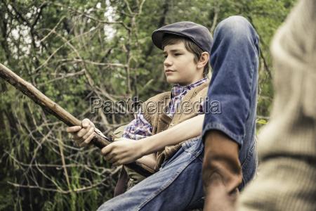 boy wearing flat cap holding branch