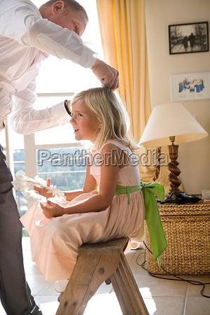 father prepares girls hair