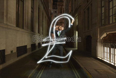young businessman light painting pound sterling