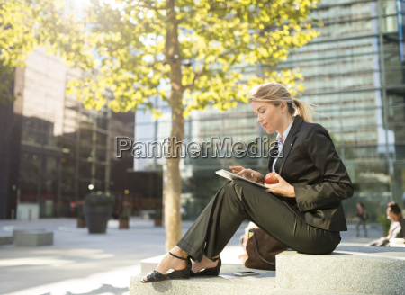 young businesswoman sitting outside city office