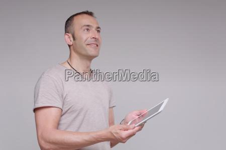 mature man holding digital tablet