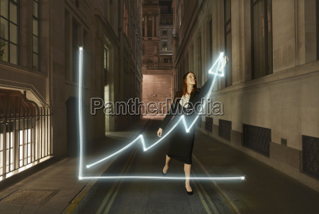 businesswoman light painting glowing chart with