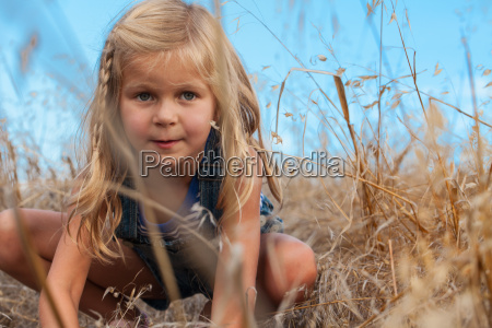 girl squatting behind tall grass