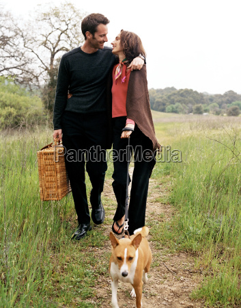 couple walking dog in countryside with