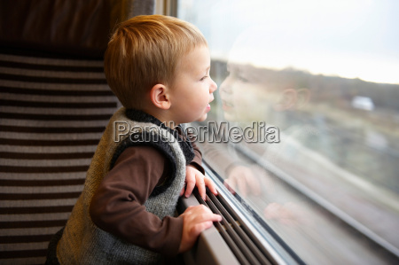 young boy looking out of train