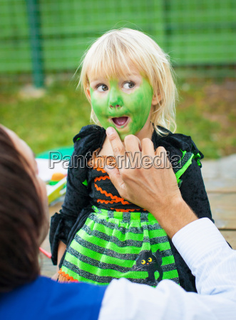 man painting childs face green