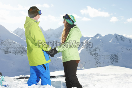couple holding hands with mountains in