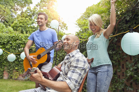 male friends playing acoustic guitar in