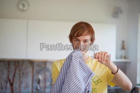 man polishing wine glass in kitchen