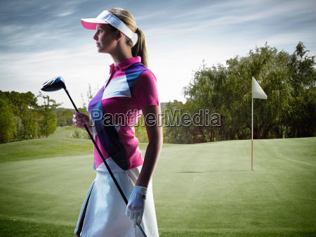 woman carrying golf club on course