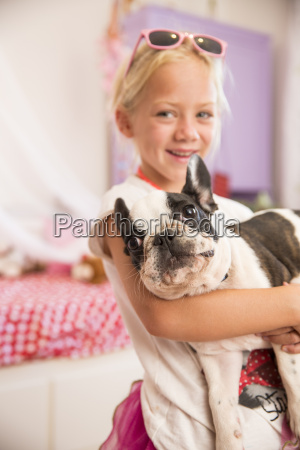 portrait of girl carrying cute dog