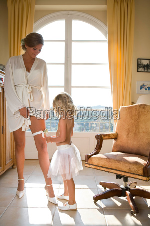 young girl looks at brides garter