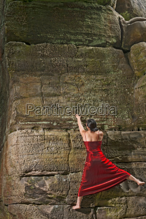 woman in red dress free climbing