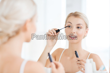 donna con mascara applicando make up