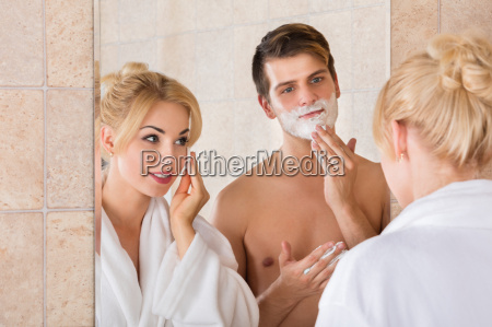 man shaving and her wife cleaning