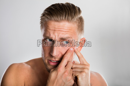 man squeezing pimple on his face