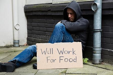 uomo triste con cartello