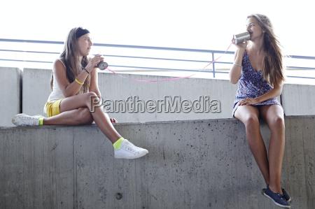 due adolescenti che utilizzano barattolo di