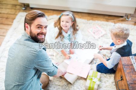 padre e figli che confezionano regali
