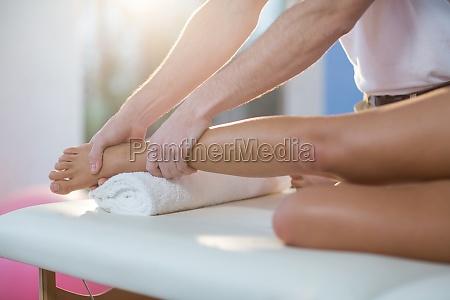 massaggio fisioterapista dando ginocchio maschio a