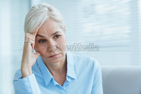 triste donna anziana a casa