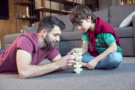 padre sorridente e concentrato figlio giocare