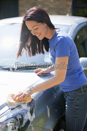 woman washing car with sponge in
