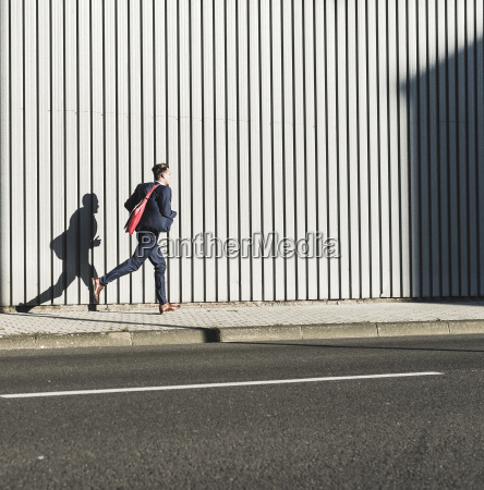 young businessman running on pavement along