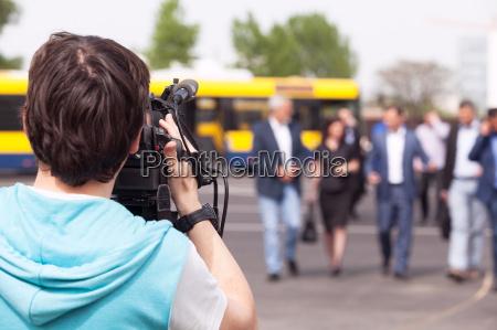 cameraman filming unrecognizable group of people