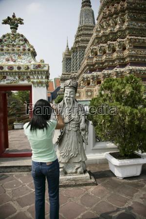 thai woman taking pictures wat po