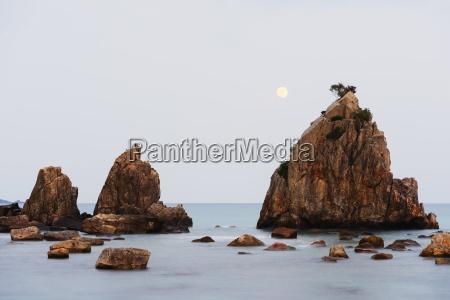 full moon rising over rock stacks