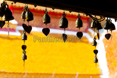 close up of prayer bells silhouetted
